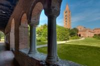 Appare improvvisa al visitatore con il suo svettante campanile nella verde pianura e dischiude inaspettati tesori di arte e di storia.